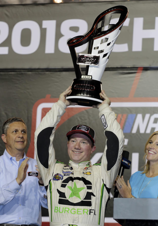 Tyler Reddick holds the trophy after winning the NASCAR Xfinity Series championship auto race at the Homestead-Miami Speedway, Saturday, Nov. 17, 2018, in Homestead, Fla. (AP Photo/Terry Renna)