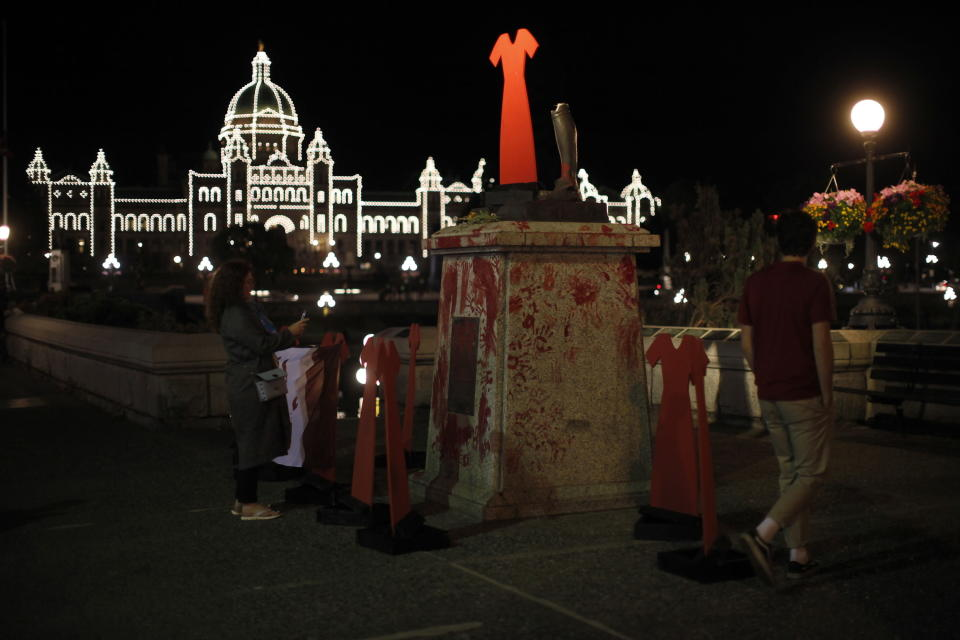 The statue of English explorer Capt. James Cook was vandalized and removed from it's base and tossed into the inner harbor and replaced with red hand prints and a red dress in protest of missing and murdered Indigenous women and girls in Victoria, Thursday, July 1, 2021. (Chad Hipolito/The Canadian Press via AP)