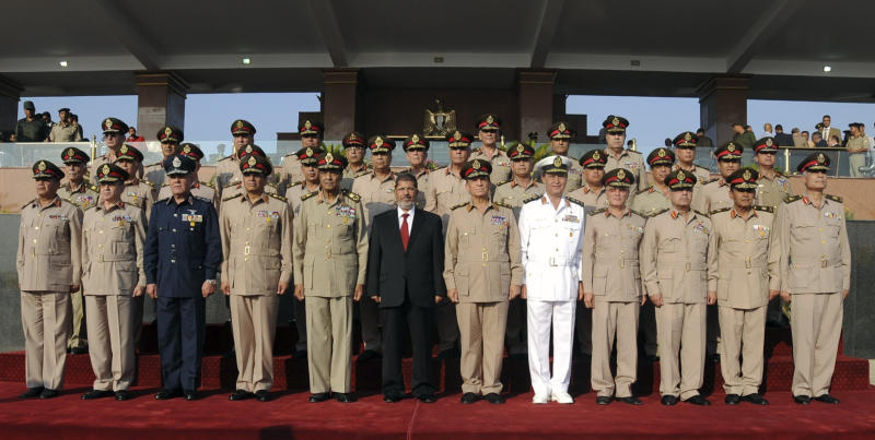 "In this image released by the Egyptian Presidency, President Mohammed Morsi, center, poses with ruling military generals at a ceremony following his inauguration, at a military base east of Cairo, Egypt, Saturday, June 30, 2012. Islamist Mohammed Morsi promised a ""new Egypt"" and unwavering support to the powerful military as he took the oath of office Saturday to become the country's first freely elected president, succeeding Hosni Mubarak who was ousted 16 months ago. (AP Photo/Egyptian Presidency)"