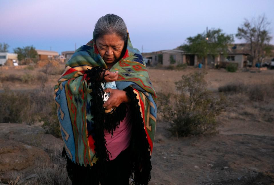 Beatrice Norton prays at sunrise while taking ground white corn in her hand in front of her home in Oraibi on the Hopi Reservation on Sept. 12, 2020. Corn is an integral part of Hopi culture and religion. Norton prays this way each morning.