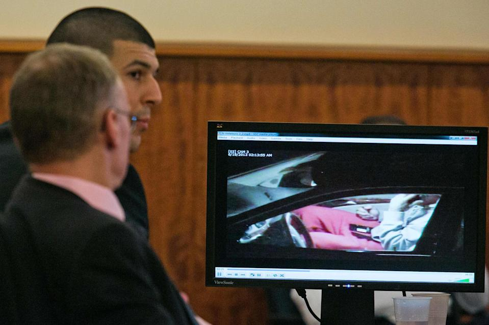Former NFL player Aaron Hernandez (C) and his attorney Charles Rankin watch surveillance video of Hernandez handling cell phones during his murder trial at the Bristol County Superior Court in Fall River, Massachusetts, February 17, 2015. REUTERS/Dominick Reuter (UNITED STATES - Tags: CRIME LAW)
