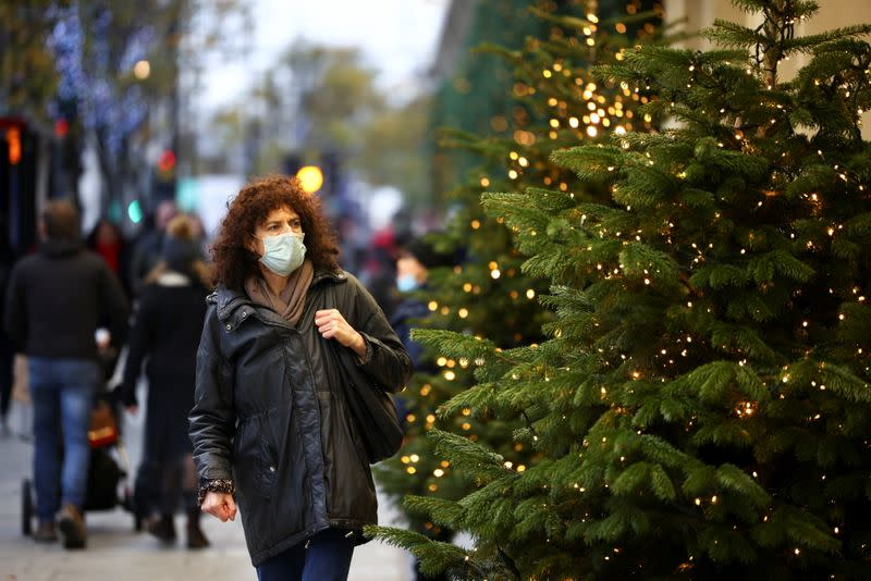 A woman walks past Christmas trees on Oxford Street, amid the coronavirus disease (COVID-19) outbreak, in London