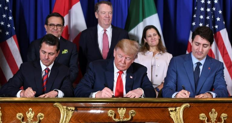 In this file photo taken on November 30, 2018, Mexican President Enrique Pena Nieto (L), US President Donald Trump (C) and Canadian Prime Minister Justin Trudeau sign a new free trade agreement in Buenos Aires