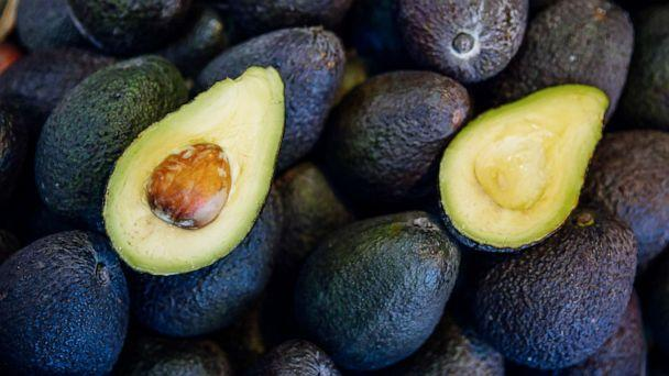 PHOTO: A freshly cut avocado lies on top of uncut avocados. (STOCK PHOTO/Getty Images)