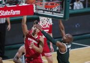 Wisconsin's Jonathan Davis, left, shoots against Michigan State's Joshua Langford during the first half of an NCAA college basketball game, Friday, Dec. 25, 2020, in East Lansing, Mich. Wisconsin won 85-76. (AP Photo/Al Goldis)