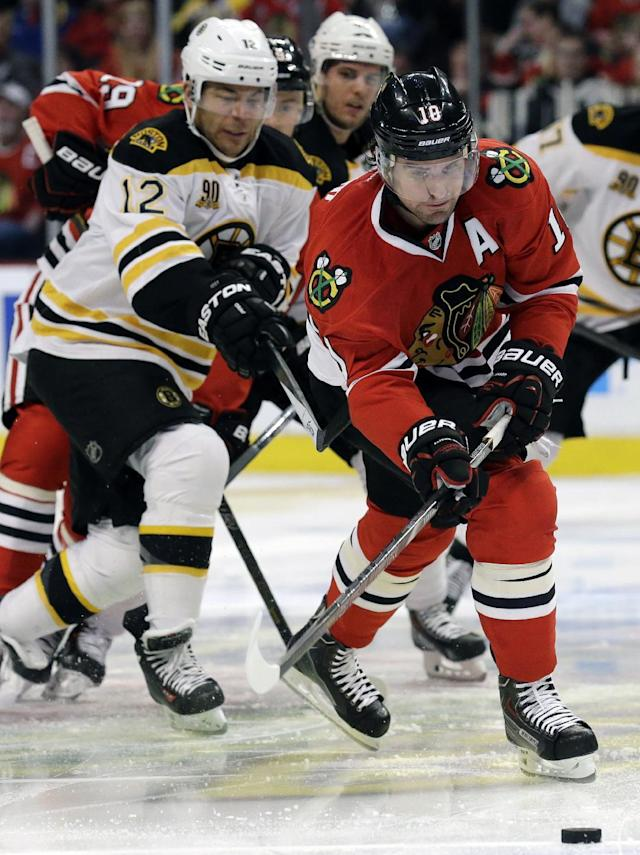 Chicago Blackhawks' Patrick Sharp (10) controls the puck against Boston Bruins' Jarome Iginla (12) during the first period of an NHL hockey game in Chicago, Sunday, Jan. 19, 2014. (AP Photo/Nam Y. Huh)
