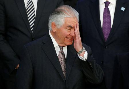 Secretary of State Tillerson wipes his face a during delegation photo in Washington