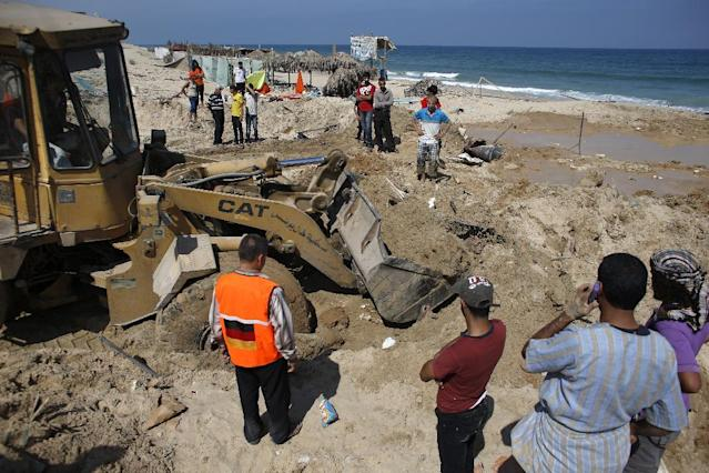 Palestinians remove debris as they search for bodies in the southern Gaza Strip on July 10, 2014 at a beach cafe hit the previous night by an Israeli air strike while people were watching the World Cup (AFP Photo/Thomas Coex)