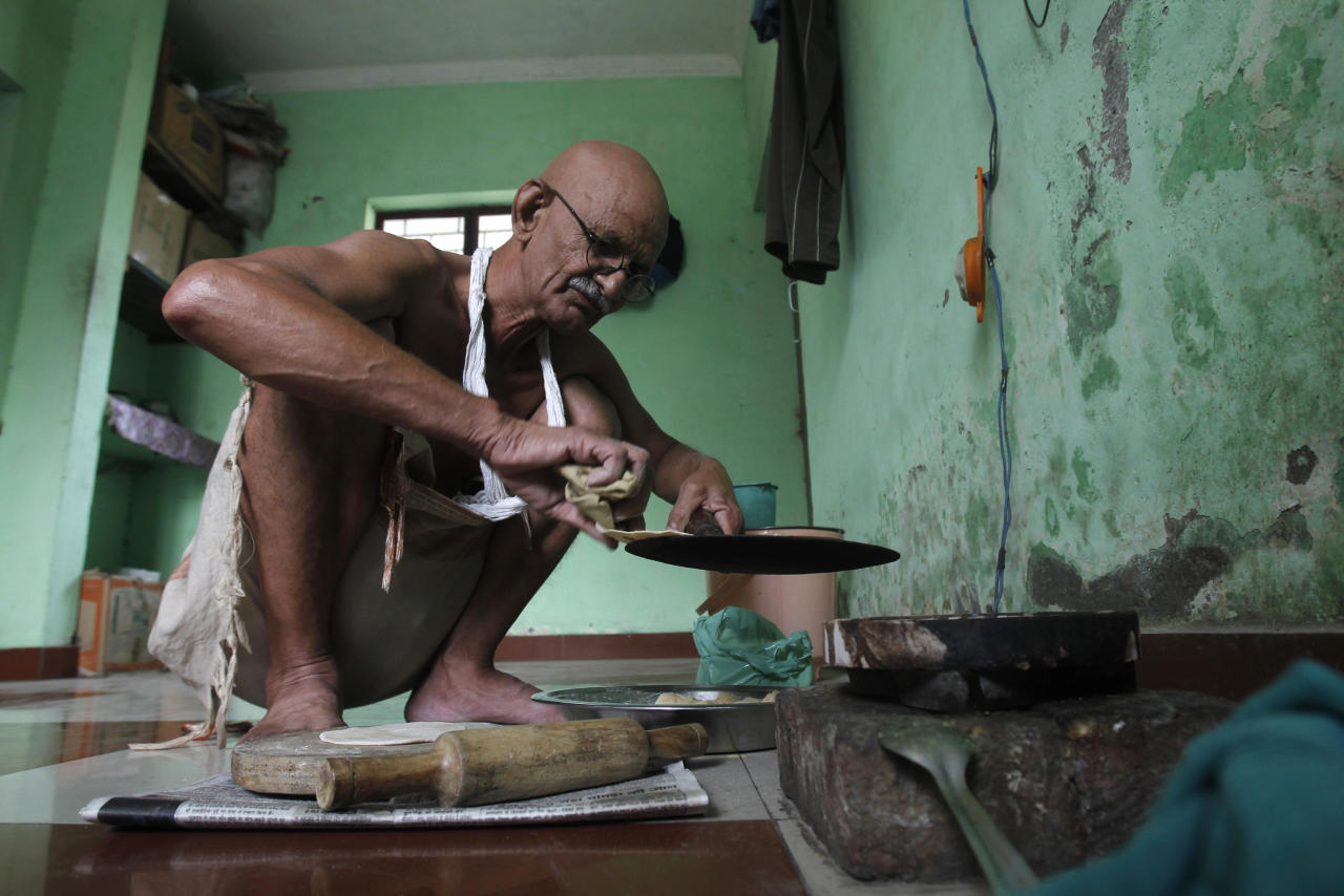 Mahesh Chaturvedi, 63, who dresses up like Mahatma Gandhi, cooks lunch at his residence in the outskirts of New Delhi October 23, 2012. Chaturvedi says that the soul of Gandhi resides in him and he has been sent to continue the work of Father of the Nation. After his self proclaimed transformation in 2002 as Gandhi, Chaturvedi has been travelling extensively and plays up to his startling resemblance to Gandhi at protests and demonstrations. Picture taken October 23, 2012. REUTERS/Mansi Thapliyal   (INDIA - Tags: SOCIETY)