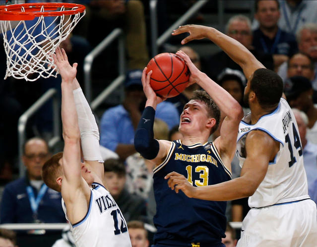 Michigan forward Moritz Wagner, center, drives to the basket between Villanova defenders Donte DiVincenzo, left, and Omari Spellman, right, during the first half in the championship game of the Final Four NCAA college basketball tournament, Monday, April 2, 2018, in San Antonio. (AP Photo/Brynn Anderson)