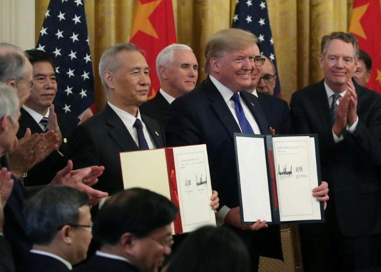 "US President Donald Trump (pictured January 15, 2020) and Chinese Vice Premier Liu He hold up signed agreements of ""phase one"" of a trade deal between the two countries"