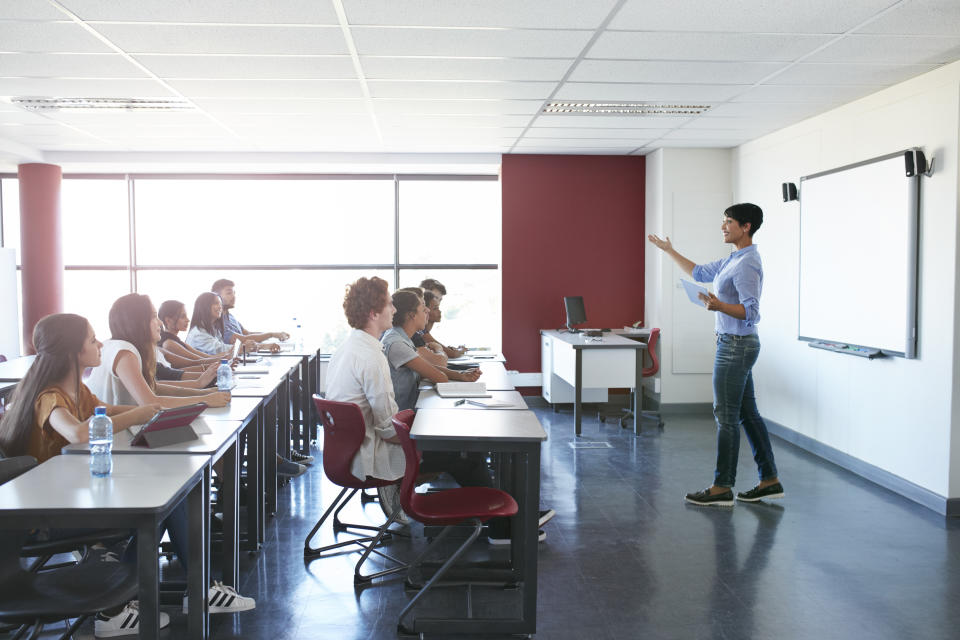 Teacher holding tablet explaning to students in classroom