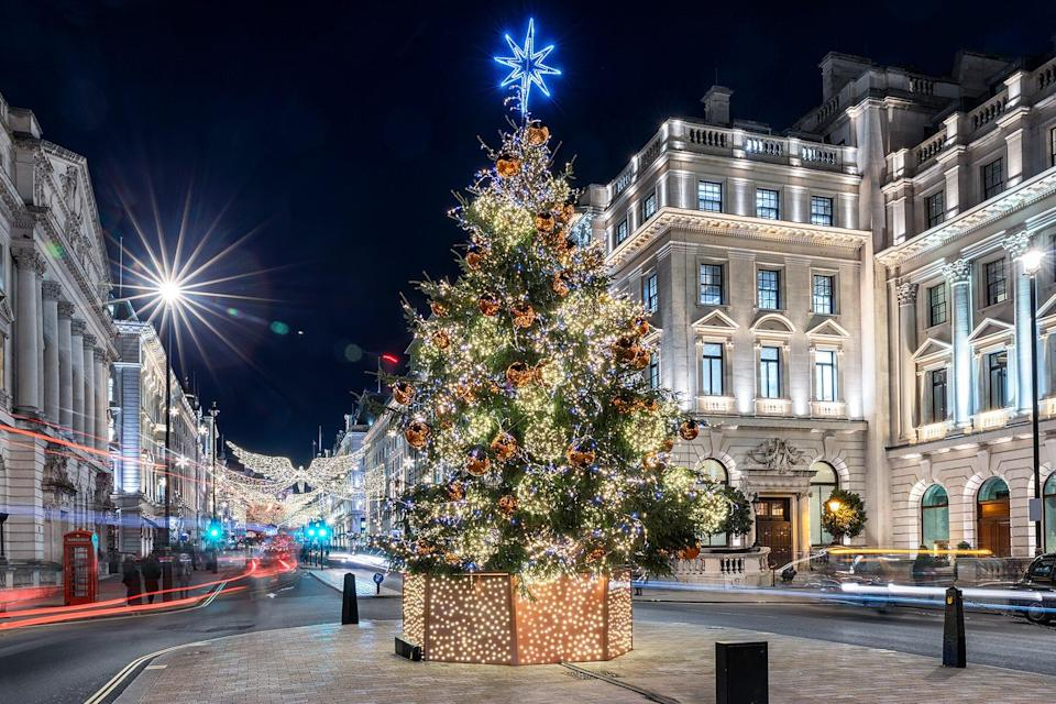 A sparkling, lit Christmas tree in the center of London, United Kingdom, during winter might time with blurred street traffic