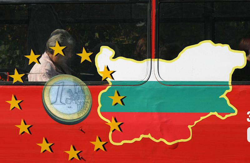 FILE - In this Sept. 25, 2006 file photo, a man reads a newspaper behind a bus window painted with the EU sign and a map of Bulgaria, in Sofia. For months, Britain's tabloid newspapers have repeatedly warned of the horrors that will ensue on Jan. 1, 2014 when work restrictions will be lifted across the European Union for migrants from Romania and Bulgaria - two of the trading bloc's newest members. (AP Photo/Petar Petrov, File)