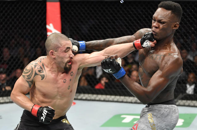 Robert Whittaker and Israel Adesanya trade punches in their UFC middleweight championship fight Saturday in Melbourne, Australia. (Getty Images)