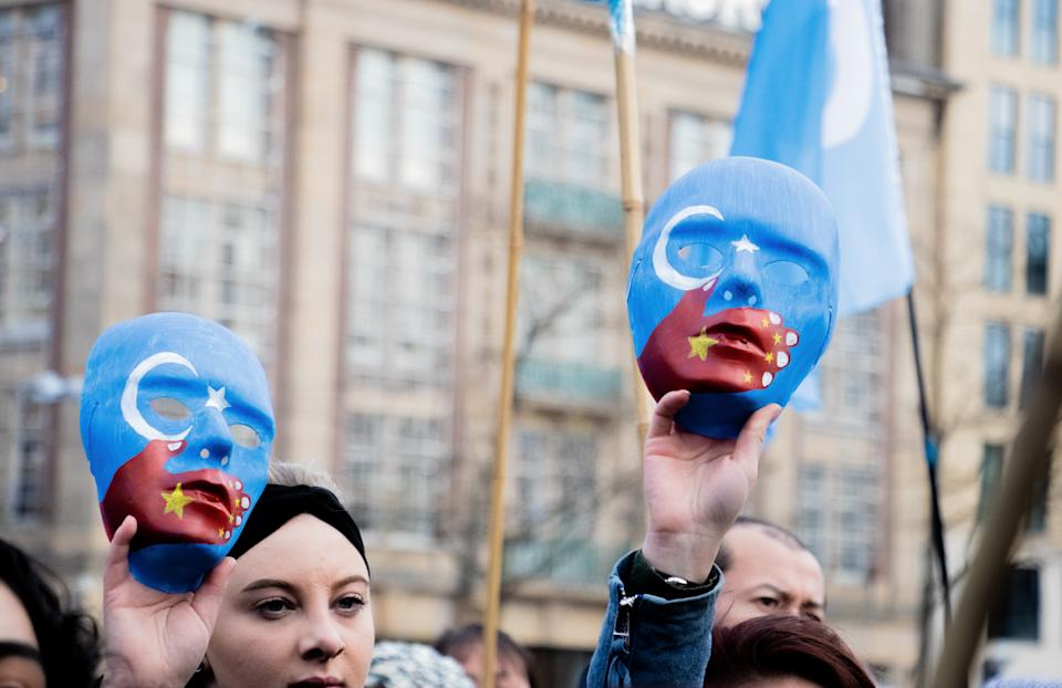 AMSTERDAM, NETHERLANDS - DECEMBER 29: People take part in a demonstration against Chinas persecution of Uighurs in Xinjiang, at Dam Square in Amsterdam, Netherlands on December 29, 2019. Chinas Xinjiang region is home to around 10 million Uighurs. The Turkic Muslim group, which makes up around 45% of Xinjiangs population, has long accused Chinas authorities of cultural, religious and economic discrimination. Up to one million people, or about 7% of the Muslim population in Xinjiang, have been incarcerated in an expanding network of political re-education camps, according to U.S. officials and UN experts. In a report last September, Human Rights Watch accused the Chinese government of carrying out a systematic campaign of human rights violations against Uighur Muslims in Xinjiang. (Photo by Abdullah Asiran/Anadolu Agency via Getty Images)