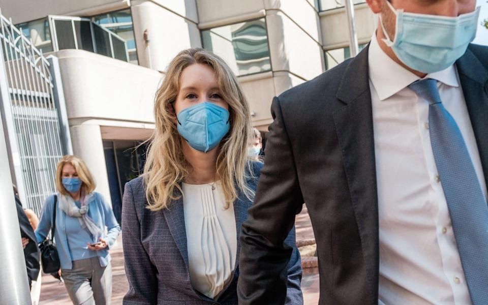 Elizabeth Holmes (L), founder and former CEO of blood testing and life sciences company Theranos, leaves the courthouse with her husband Billy Evans - NICK OTTO/AFP