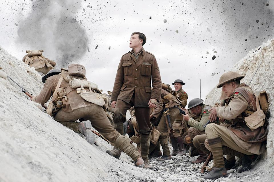 Lance Corporal William Schofield standing in a trench in his uniform with other uniformed soldiers around him