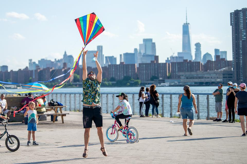 NEW YORK, NEW YORK - MAY 30: A person jumps trying to make a kite fly at Gantry Plaza State Park, Long Island City on May 30, 2020 in New York City. Government guidelines encourage wearing a mask in public with strong social distancing as all 50 US states have begun to slowly reopen after weeks of stay-at-home measures to control the spread of COVID-19.
