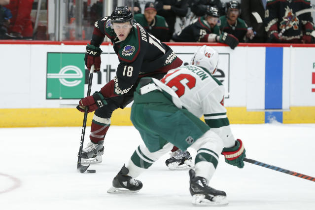 Arizona Coyotes left wing Christian Dvorak (18) carries the puck in front of Minnesota Wild left wing Jason Zucker in the second period during an NHL hockey game, Saturday, Nov. 9, 2019, in Glendale, Ariz. (AP Photo/Rick Scuteri)