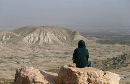 A Palestinian man sits on a rock at Jordan Valley near the West Bank city of Jericho January 21, 2016.  REUTERS/Mohamad Torokman