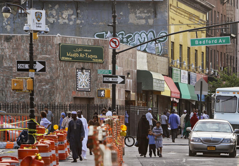 In this photo made Aug. 18, 2011, people pass below a New York Police security camera, upper left, situated above a mosque on Fulton St., in the Brooklyn neighborhood of Bedford-Stuyvesant in New York. After the attacks of Sept. 11, the New York Police Department has dispatched teams of undercover officers into minority neighborhoods and used informants to monitor sermons at mosques, even when there's no evidence of wrongdoing.   (AP Photo/Bebeto Matthews)