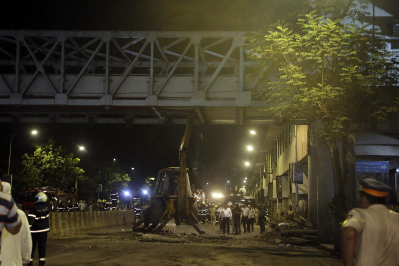 A crane works to remove a pedestrian bridge after a part of it collapsed in Mumbai, India, Thursday, March 14, 2019. A pedestrian bridge connecting a train station with a road collapsed in Mumbai on Thursday, killing at least five people and injuring more than 30, police said. (AP Photo/Rajanish Kakade)