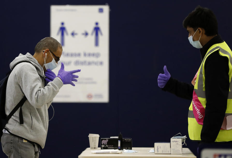 FILE - In this Tuesday, June 9, 2020 file photo a London Underground worker, right, hands over a free face mask, gloves and hand sanitizer to a passenger at London's Baker Street station. (AP Photo/Frank Augstein, File)