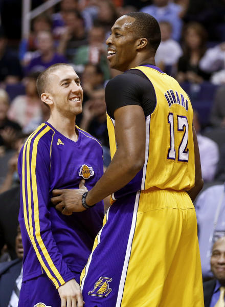 Los Angeles Lakers' Dwight Howard (12) laughs along with teammate Steve Blake after Howard missed a dunk against the Phoenix Suns in the first half of an NBA basketball game on Monday, March 18, 2013, in Phoenix. (AP Photo/Ross D. Franklin)