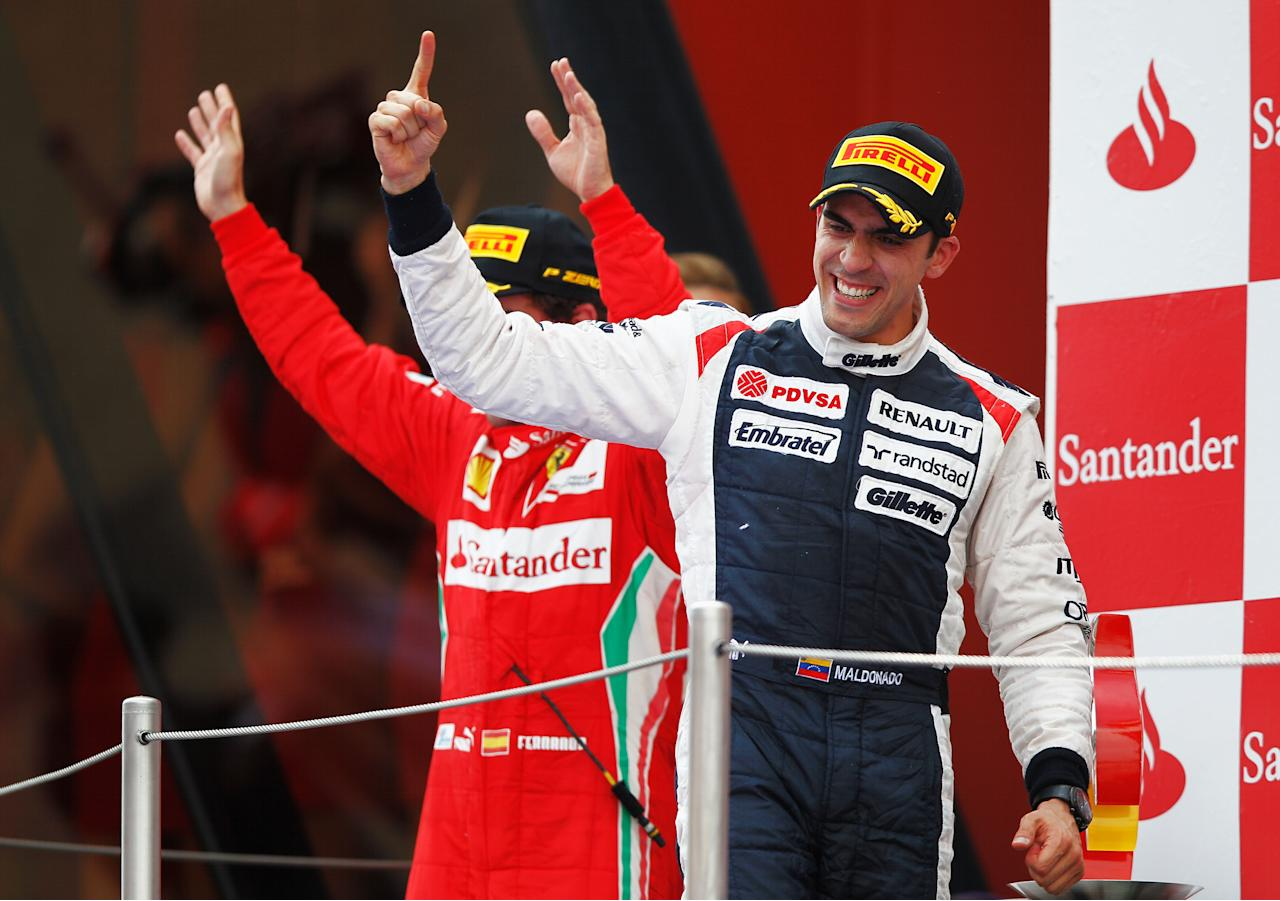 BARCELONA, SPAIN - MAY 13:  Race winner Pastor Maldonado (R) of Venezuela and Williams celebrates with second placed Fernando Alonso (L) of Spain and Ferrari on the podium following the Spanish Formula One Grand Prix at the Circuit de Catalunya on May 13, 2012 in Barcelona, Spain.  (Photo by Paul Gilham/Getty Images)