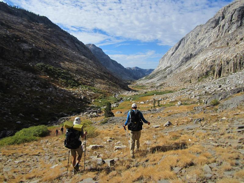 This Sept. 20, 2012 photo shows hikers making their way through an area of Yosemite National Park that lacks trails in Stubblefield Canyon. Outdoor adventurer Andrew Skurka, pictured on the right, has hiked tens of thousands of miles alone in wild areas across the U.S., and now shares his knowledge by leading guided trips for others interested in backcountry hikes. (AP Photo/John Pain)