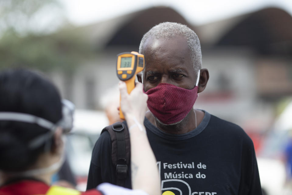 A member of the Red Cross checks the temperature of a worker at the CEASA, Rio de Janeiro's main wholesale market, amid the new coronavirus pandemic in Rio de Janeiro, Brazil, Tuesday, June 23, 2020. (AP Photo/Silvia Izquierdo)