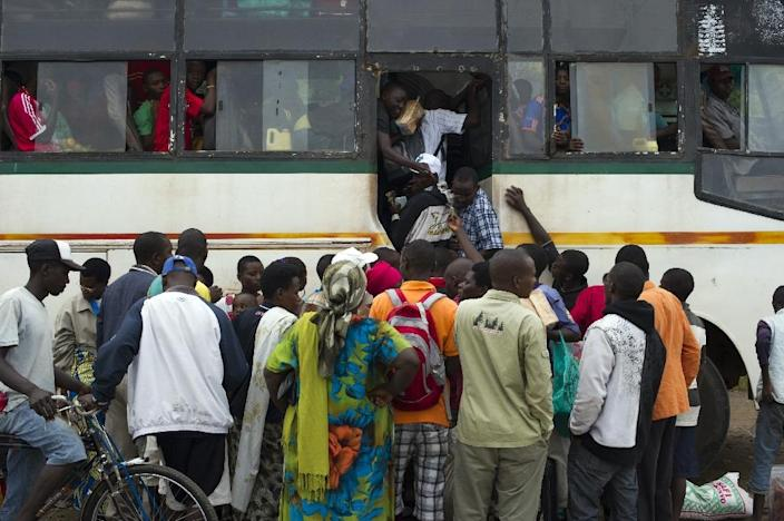 People board a bus leaving Bujumbura on May 9, 2015 after the movement of protest followed by violent clashes which left at least eighteen dead (AFP Photo/Phil Moore)