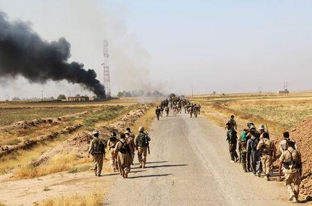 Kurdish Peshmerga fighters walk with their weapons as smoke rises from the site of clashes, south of Daquq