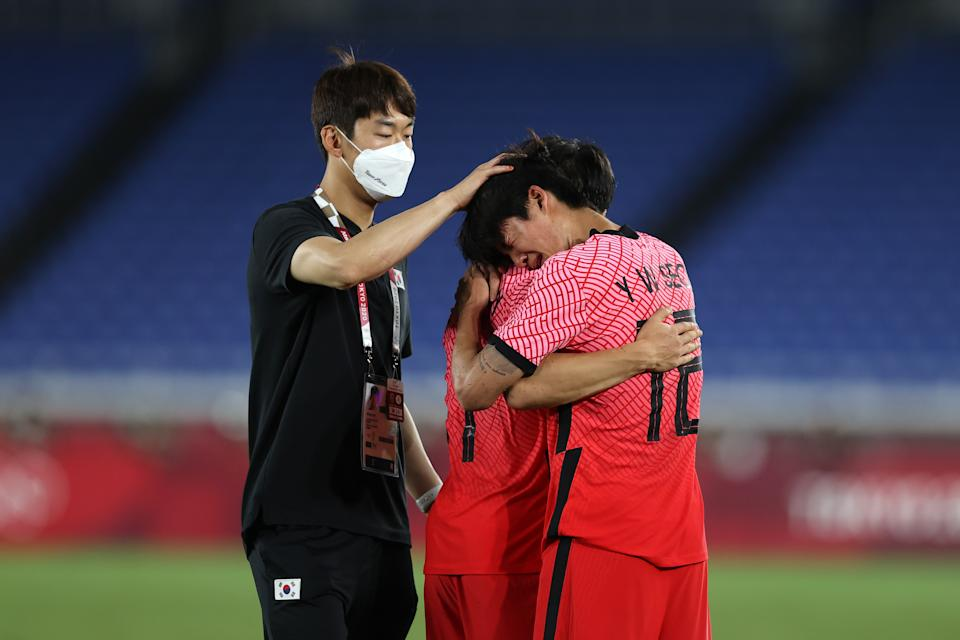 YOKOHAMA, JAPAN - JULY 31: Youngwoo Seol #12 of Team South Korea looks dejected as he is consoled by teammates following defeat in the Men's Quarter Final match between Republic Of Korea and Mexico on day eight of the Tokyo 2020 Olympic Games at International Stadium Yokohama on July 31, 2021 in Yokohama, Kanagawa, Japan. (Photo by Francois Nel/Getty Images)