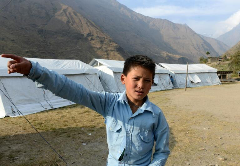 Nepalese schoolboy Dawa Phunchok Lama gestures as he stands near the Shree Buddha Secondary School in the village of Sirdibas in Gorkha District