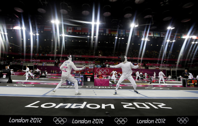 FILE - In this Saturday, Aug. 11, 2012 file photo Cao Zhongrong of China, left, and Ondrej Polivka of the Czech Republic compete during the fencing section of the men's modern pentathlon at the 2012 Summer Olympics, in London. Removing a sport from the Olympics is one of the IOC's most delicate and sensitive tasks. After months of evaluation, a decision will come next week _ and the century-old competition of modern pentathlon appears the most at risk. The IOC executive board will meet in Lausanne, Switzerland, and announce Tuesday which of the current 26 sports on the Olympic program will be dropped for the 2020 Games. (AP Photo/Kirsty Wigglesworth, File)