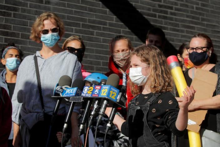 A child speaks to the press during a protest to the closing of Public School 130 outside the school building for safety reasons, following the outbreak of the coronavirus disease (COVID-19) in Brooklyn, New York