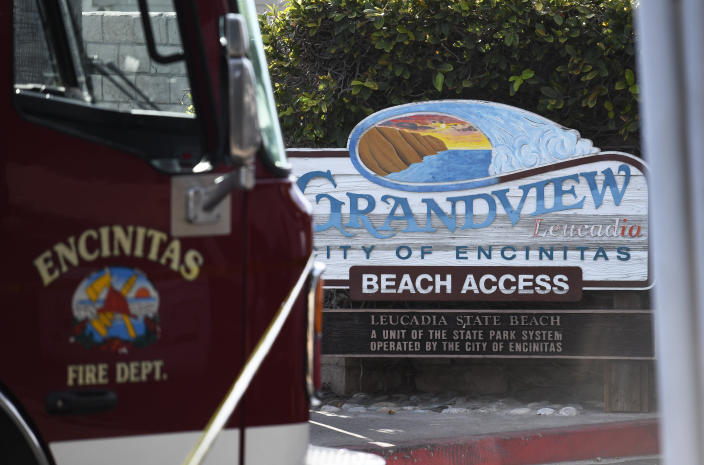 A fire truck sits above the site of a cliff collapse at a popular beach Friday, Aug. 2, 2019, in Encinitas, Calif. At least one person was reportedly killed, and multiple people were injured, when an oceanfront bluff collapsed Friday at Grandview Beach in the Leucadia area of Encinitas, authorities said. (AP Photo/Denis Poroy)