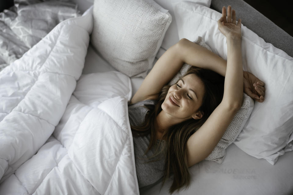 Woman stretching in bed after wake up. Beautiful girl enjoying morning light.