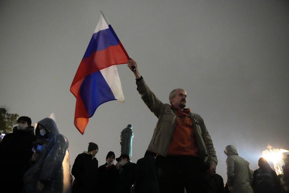 A demonstrator holds a Russian national flag during a protest against the results of the Parliamentary election in Moscow, Russia, Monday, Sept. 20, 2021. The results in the other six regions that were allowed to vote online have been detailed. In Moscow, approval of the ruling party has always been particularly low and protest voting has been widespread. Candidates from the Communist Party called for demonstrations later in the day. (AP Photo/Pavel Golovkin)