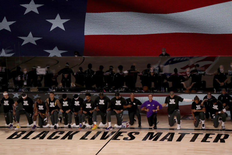 Black Lives Matter written on the court with players kneeling while locking arms and an American flag behind them.