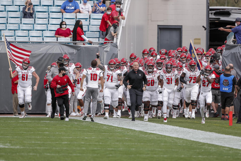 JACKSONVILLE, FL - JANUARY 2: Head Coach Dave Doeren of the North Carolina State Wolfpack leads his team on to the field before the start of the game against the University of Kentucky Wildcats at the 76th annual TaxSlayer Gator Bowl at TIAA Bank Field on January 2, 2021 in Jacksonvile, Florida.  (Photo by Don Juan Moore/Getty Images)