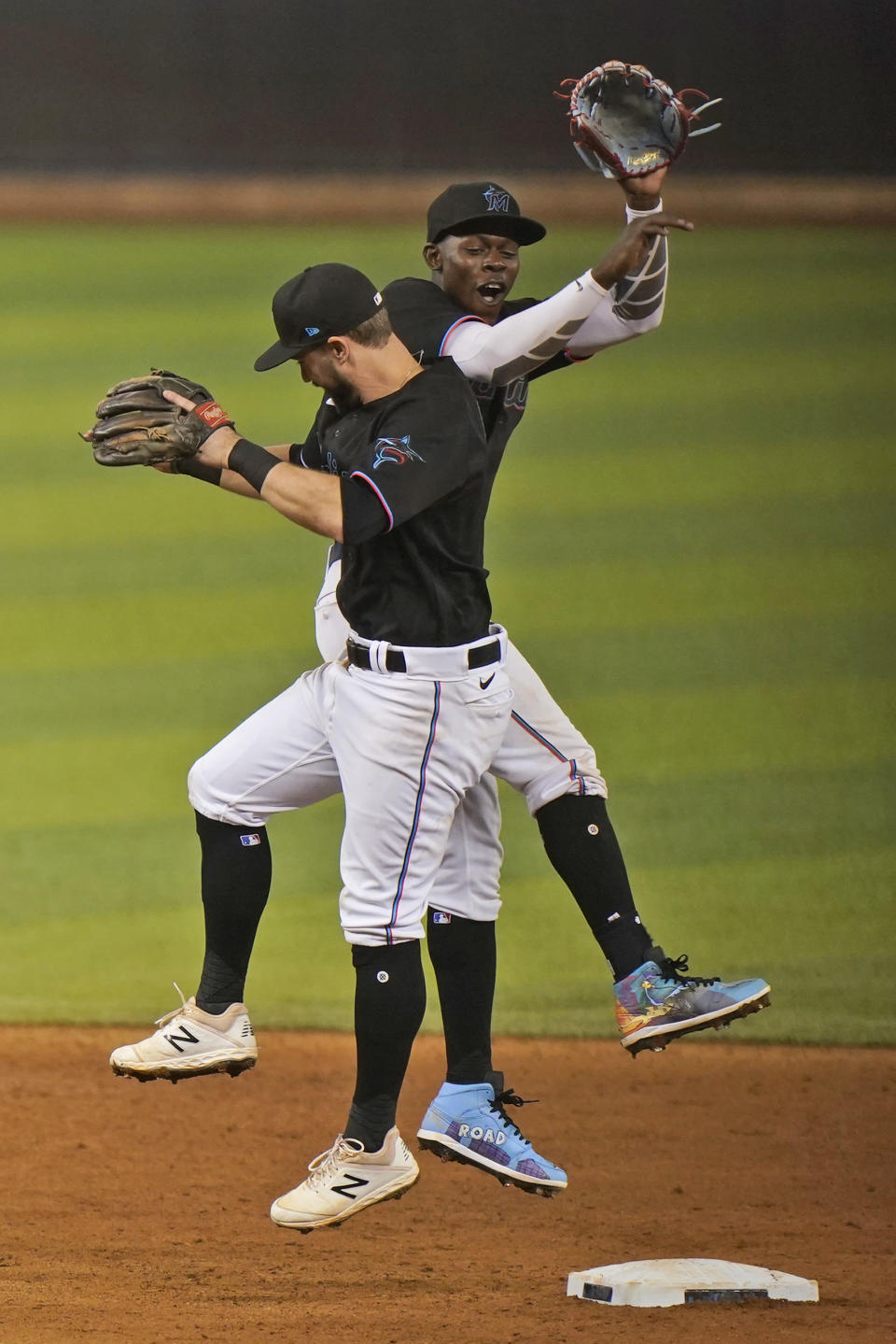 Miami Marlins' Jon Berti, foreground, and Jazz Chisholm Jr. celebrate after they defeated the Atlanta Braves in a baseball game, Saturday, June 12, 2021, in Miami. (AP Photo/Wilfredo Lee)