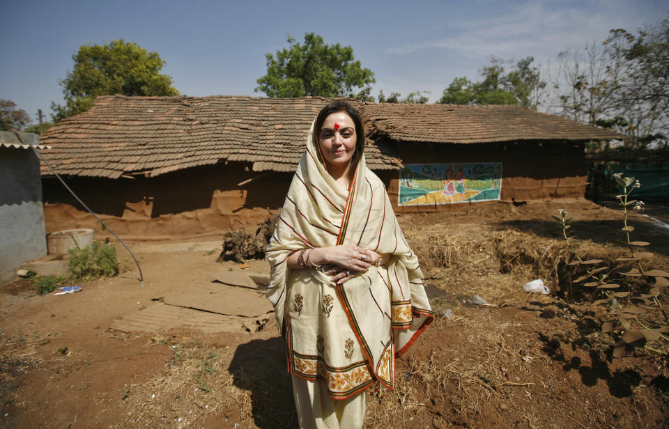 Nita Ambani, Chairperson of Reliance Foundation and wife of Mukesh Ambani Chairman and Managing Director of Reliance Industries, poses in front of a hut during a