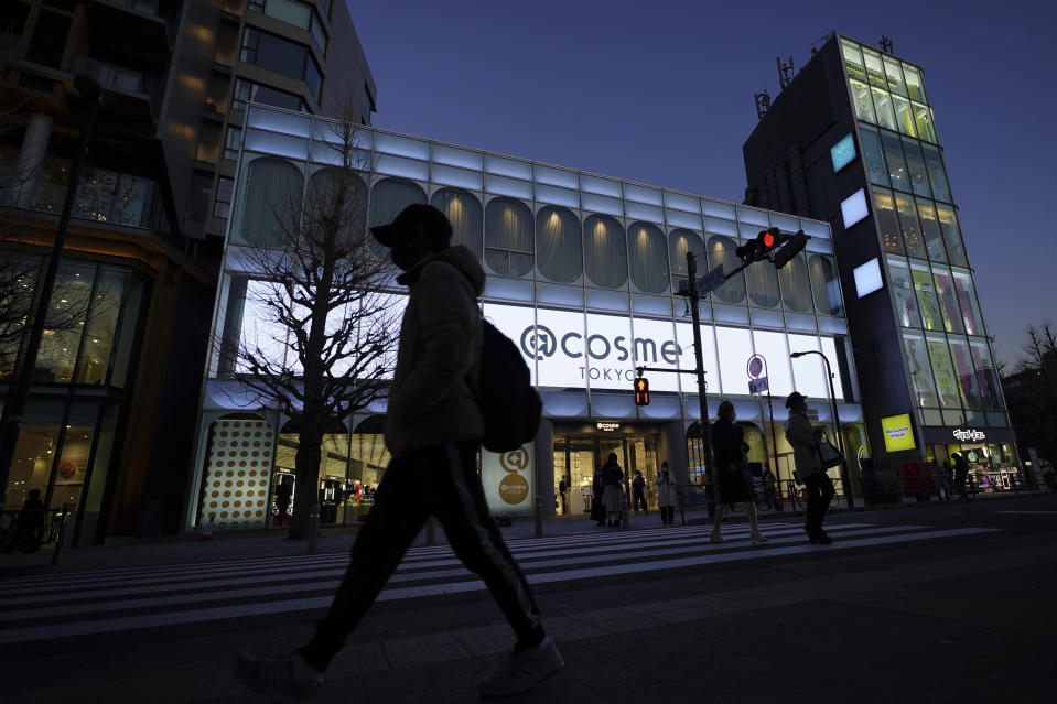 People walk past @cosme TOKYO, a store selling a selection of cosmetics and makeup products including men's cosmetic, in Tokyo's Harajuku district Tuesday, Feb. 9, 2021. The coronavirus pandemic has been pushing businesses to the edge in Japan, but some in the men's beauty industry have seen an unexpected expansion in their customer base. Japanese businessmen in their 40s, 50s and 60s who had little interest in cosmetics before the pandemic are now buying makeup. (AP Photo/Eugene Hoshiko)