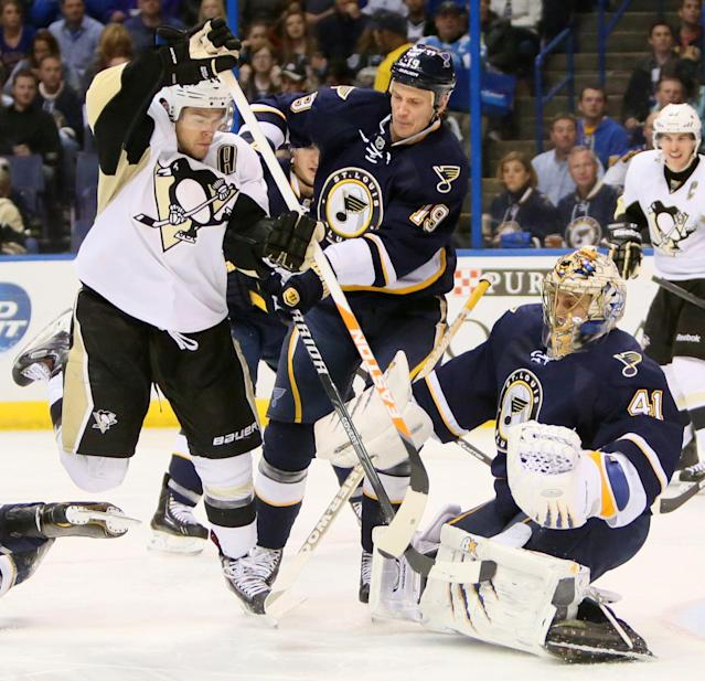 Pittsburgh Penguins left wing Chris Kunitz, left, is defended by St. Louis Blues defenseman Jay Bouwmeester (19) and goaltender Jaroslav Halak in second-period NHL hockey game action on Saturday, Nov. 9, 2013, in St. Louis. (AP Photo/St. Louis Post-Dispatch, Chris Lee)