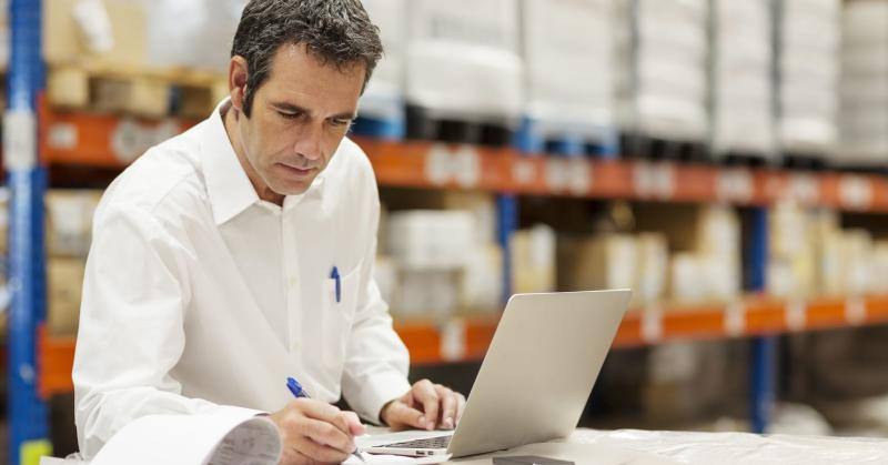 Supervisor doing paperwork while using laptop in warehouse