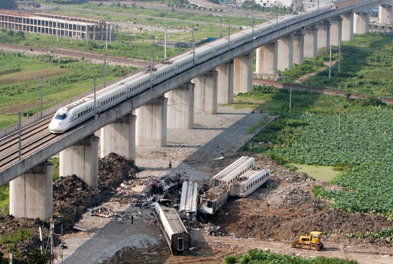 A bullet train passes the wreckage of two other high-speed trains which collided two days earlier, in Shuangyu, eastern China on July 25, 2011 (AFP Photo/Str)