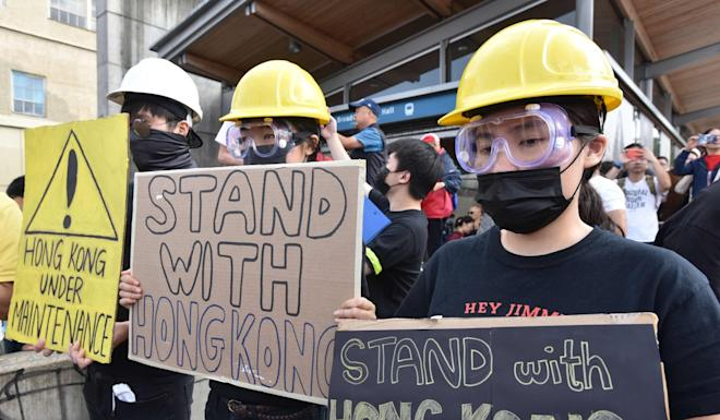 Demonstrators hold signs in support of the Hong Kong democracy movement at the Broadway train station in Vancouver on August 17. Photo: AFP